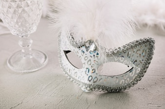 Close-up of a masquerade carnival feather mask with empty glass over concrete background