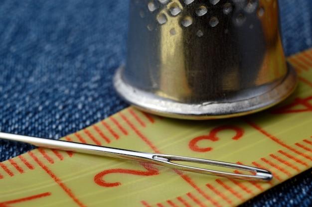 針で巻尺と指ぬきのクローズアップ。