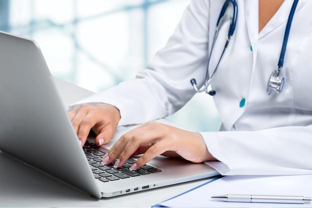 노트북에 입력하는 의료 종사자의 클로즈업