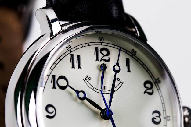 白い背景で隔離の男性の腕時計のクローズアップ。