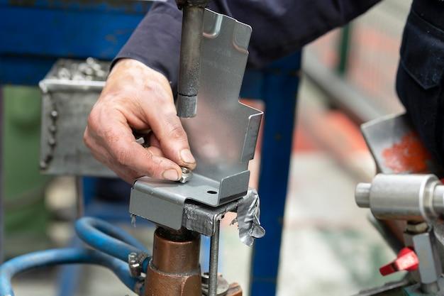 공장 작업자가 스폿 용접하는 금속 요소를 닫습니다. 산업 개념입니다.