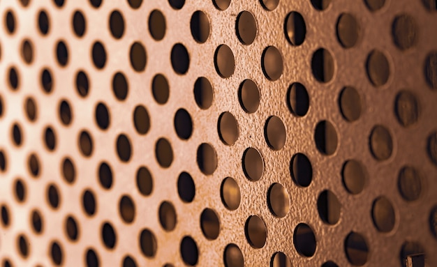 둥근 구멍이있는 금속 그릴의 클로즈업은 다양한 목적을위한 초강력 첨단 장비를 생산할 때 컴퓨터 케이스를 덮습니다.