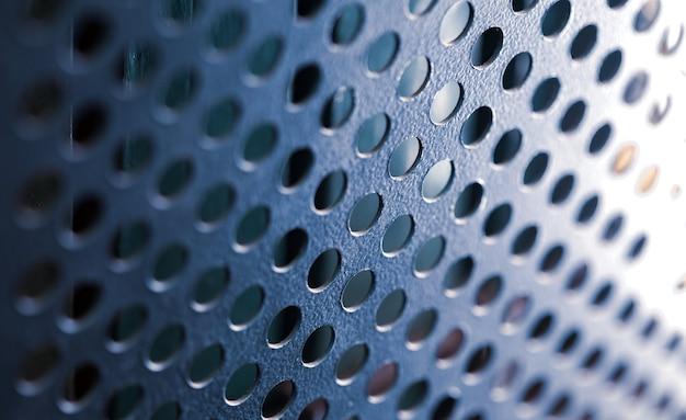 丸い穴のある金属グリルのクローズアップがコンピュータケースを覆っている
