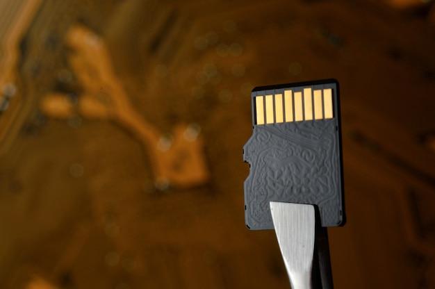핀셋으로 고정 된 마이크로 회로에 대한 마이크로 sd 메모리 카드의 클로즈업.
