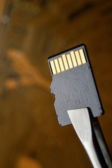 ピンセットで固定された、マイクロサーキットに対するマイクロsdメモリーカードの拡大図。