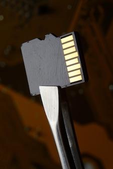 핀셋으로 고정 된 마이크로 회로의 배경에 마이크로 sd 메모리 카드의 클로즈업.