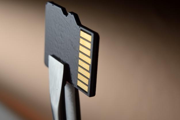 핀셋으로 고정 된 micro sd 메모리 카드의 클로즈업.