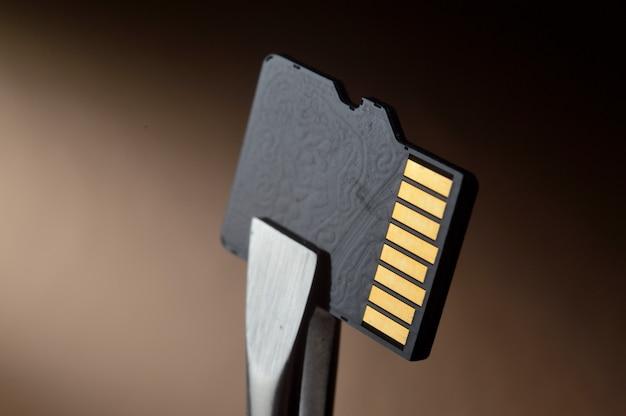 핀셋으로 고정 된 micro sd 메모리 카드의 확대 그림입니다.