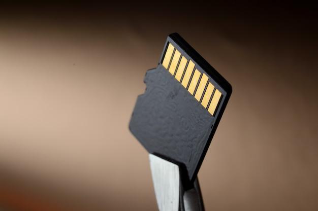 핀셋이있는 micro sd 메모리 카드의 클로즈업