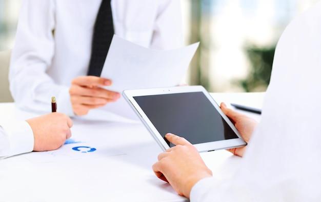 タブレットコンピューターを使用して仕事をしている現代のビジネスチームのクローズアップ