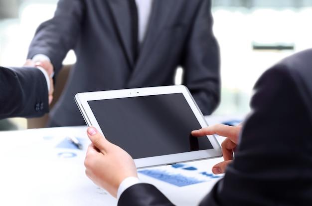 Крупный план современной бизнес-команды, использующей планшетный компьютер для работы