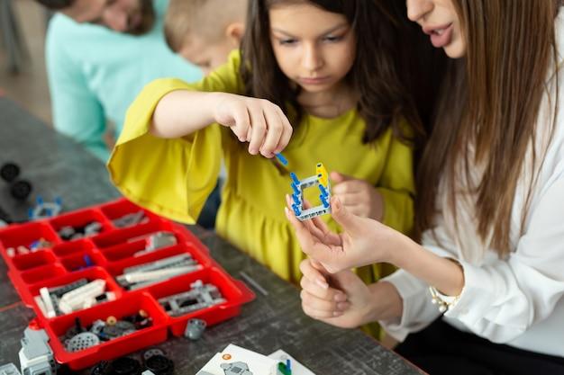 建設キットから制御されるロボットを作る学校での母と娘の手のクローズアップ。