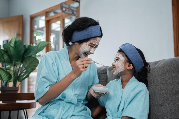 소파에 앉아있는 동안 어머니와 그녀의 어린 소녀가 서로를보고 얼굴 마스크를 쓰고 웃고 닫습니다