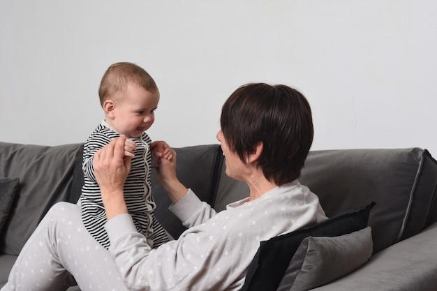 自宅のソファで赤ちゃんと遊んでいる母親のクローズアップパジャマを持っている人