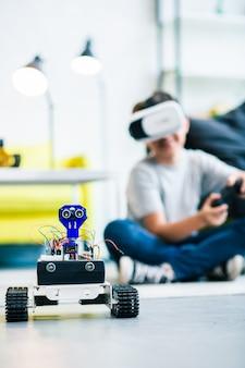 小さな賢い男の子がそれをテストしている間、床にある可動式の手作りロボットのクローズアップ