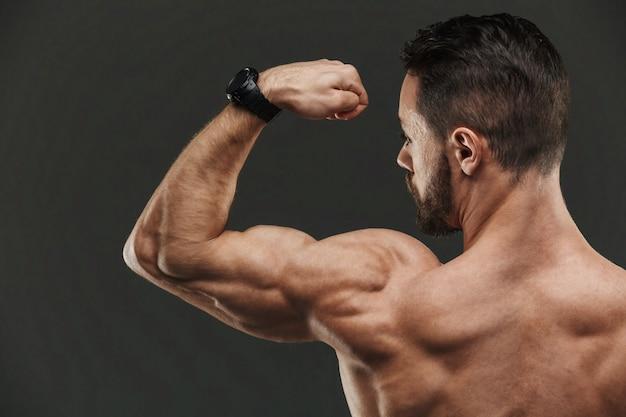 上腕二頭筋を曲げる筋肉ボディービルダーのクローズアップ