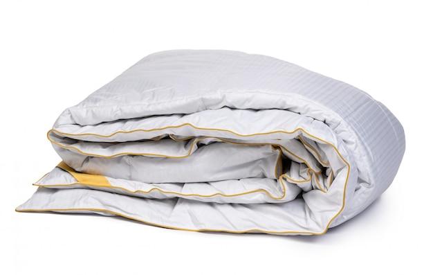 Закройте вверх нового одеяла изолированного на белой поверхности
