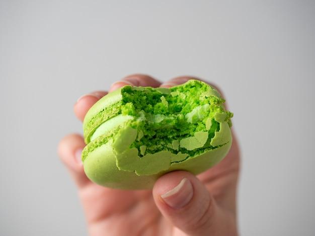白い背景の手にかじった緑のマカロンクッキーのクローズアップ