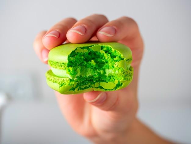 白い背景の上のあなたの手でかじった緑のマカロンクッキーのクローズアップ