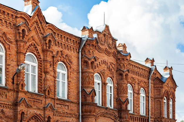 古い家のクローズアップは、夏の日に青い空を背景に白い窓と古いレンガで作られた大邸宅