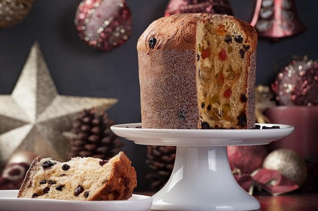Закройте панеттоне на белой тарелке с ломтиком, подаваемым сбоку, фон с расфокусированным и ненасыщенным рождественским украшением.