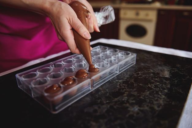 キャンディーバッグを持って、液体の温かいチョコレートの塊をキャンディーの型に押し込むパティシエの手のクローズアップ。手作りの贅沢なチョコレートを作るプロセス。