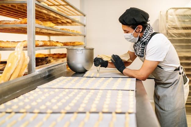 과자 가게에서 크림을 짜내는 과자 봉지가있는 과자 요리사의 근접