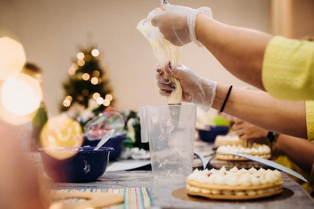 クリスマスのジンジャーブレッドを絞り袋で飾るペストリーの手のクローズアップ、作業環境。肩越しの景色。