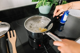 Close-up of a person boiling rigatoni pasta in the saucepan over the electric stove