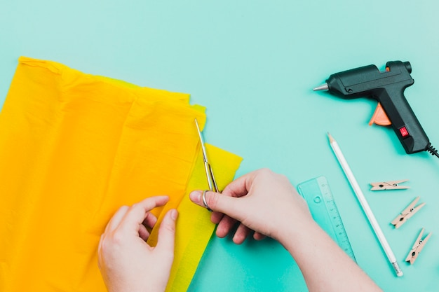 ターコイズブルーの背景にはさみで黄色い紙を切る人のクローズアップ