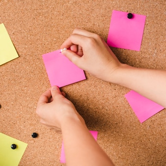 Close-up of a person fixing pink adhesive note with thumbtack on corkboard