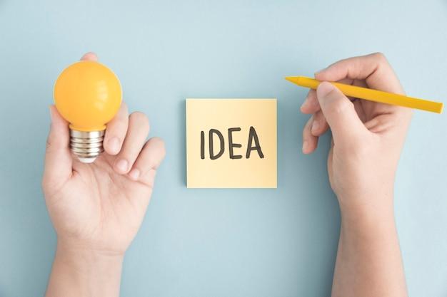 灰色の背景の上に付箋の上にアイデアのテキストと黄色のクレヨンと電球を持っている人のクローズアップ
