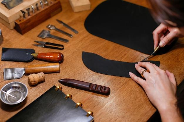 워크샵에서 가죽 제품을 만드는 사람의 클로즈업