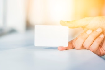 Close-up of a person's hand holding blank white card