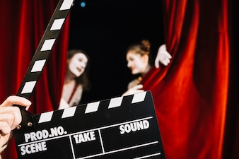 Close-up of a person's hand holding clapperboard