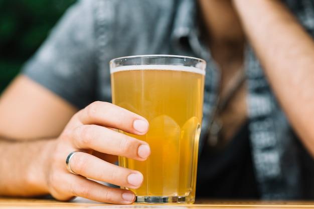 Крупным планом рука человека, держащего стакан пива