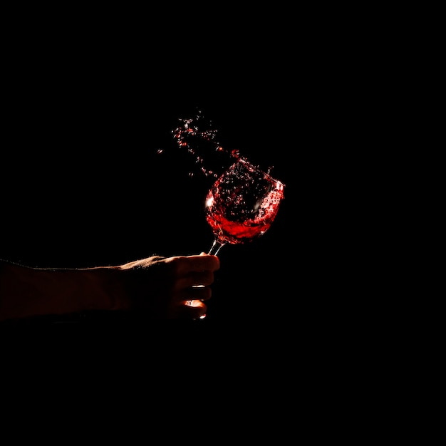 Крупным планом рука человека, проведение стакан красного вина, брызги из стекла