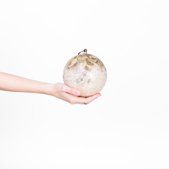 Close-up of a person's hand holding globe pendulum on white background