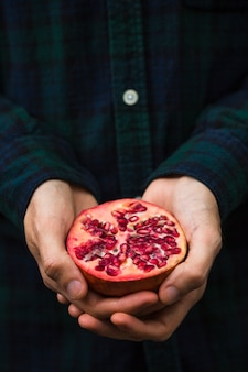 Close-up of a person's hand holding halved pomegranate