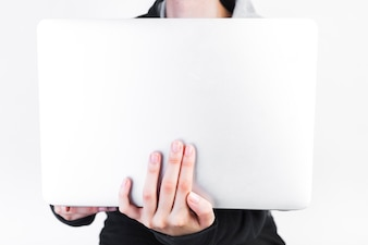 Close-up of a person's hand holding laptop