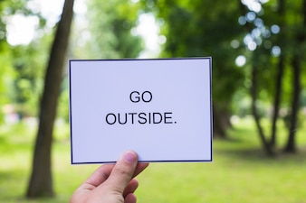 Close-up of a person's hand holding placard with go outside text