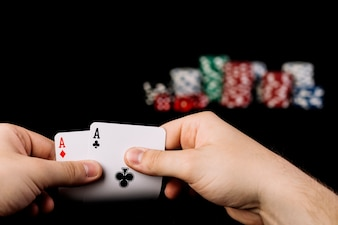 Close-up of a person's hand holding two aces playing cards