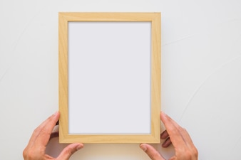 Close-up of a person's hand holding white wooden frame on wall