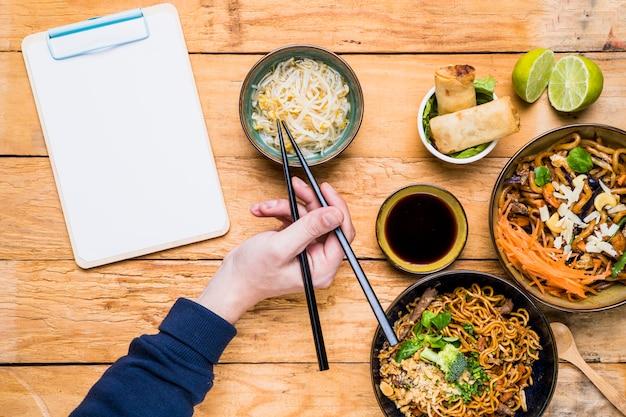 テーブルの上の箸でもやしを拾う人の手のクローズアップ