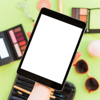 Close-up of a person's hand showing blank digital tablet screen over cosmetics