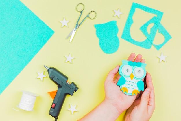 黄色の背景に手作りの青い紙かわいいフクロウを示す人の手のクローズアップ