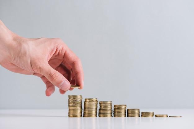 Крупным планом рука человека, укладывая золотые монеты