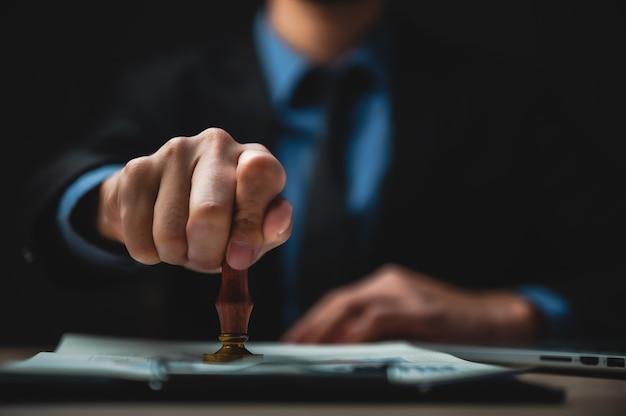 Крупный план руки человека с утвержденным штампом на документе на столе