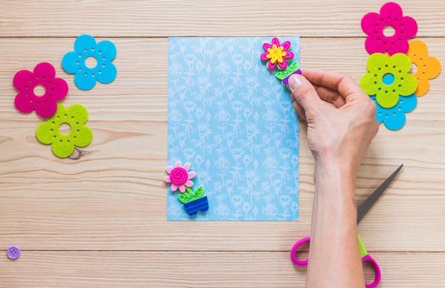スクラップブックカードに花の鍋のパッチを貼って人の手のクローズアップ