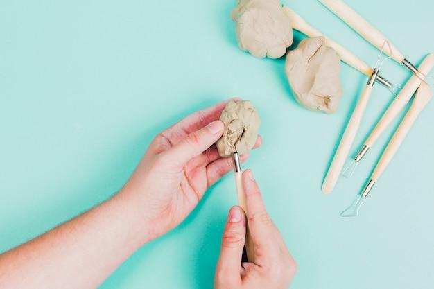 민트 녹색 배경에 조각 도구를 사용하여 사람의 손의 근접
